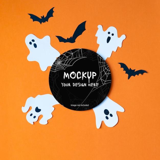 オレンジ色の背景にハロウィーンの装飾的な幽霊とコウモリのテンプレート黒丸レイアウトモックアップ