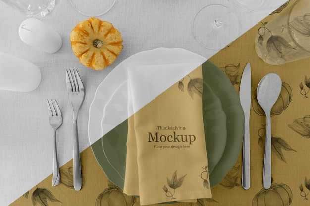 Thanksgiving dinner table arrangement with cutlery and pumpkin