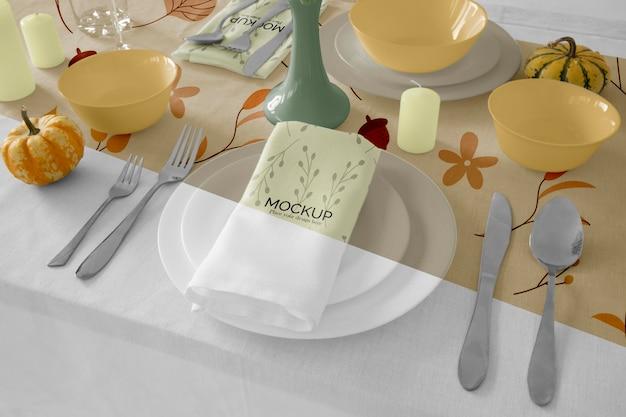 Обеденный стол на день благодарения с салфеткой на тарелке и столовыми приборами