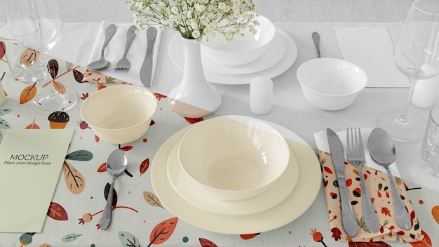 Thanksgiving dinner table arrangement with plates and flower vase