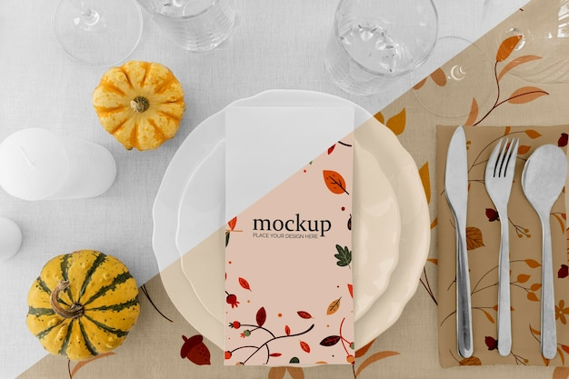 Thanksgiving dinner table arrangement with plates and pumpkins