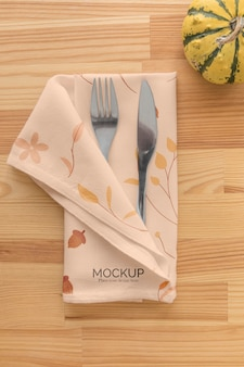 Thanksgiving dinner table arrangement with pumpkin and cutlery in napkin