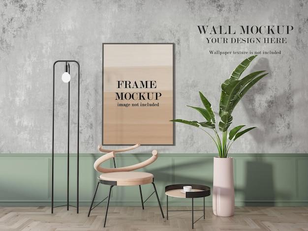 Тонкая серая рамка на серой стене рядом с растением