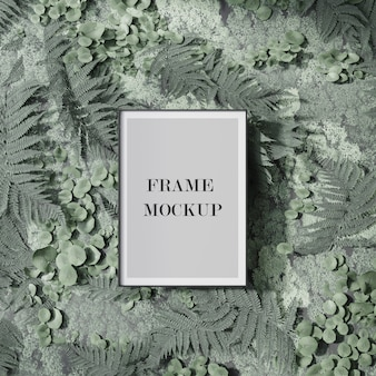 Thin poster and picture frame mockup on green plant wall