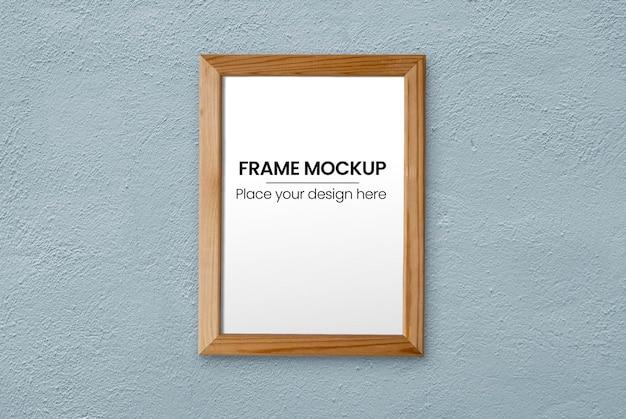 青い壁のモックアップ上の薄い木製フレーム