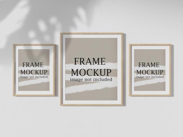 Три рамки для плакатов, висящие на стене, с падающей на них тенью дерева