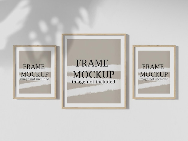 Three poster frames hanging on wall with tree shadow falling on them