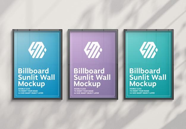 Три вертикальных рекламных щита, висящие на солнечной стене, макет