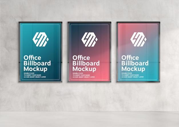 햇볕에 쬐인 벽에 걸려있는 세 개의 수직 광고판 모형