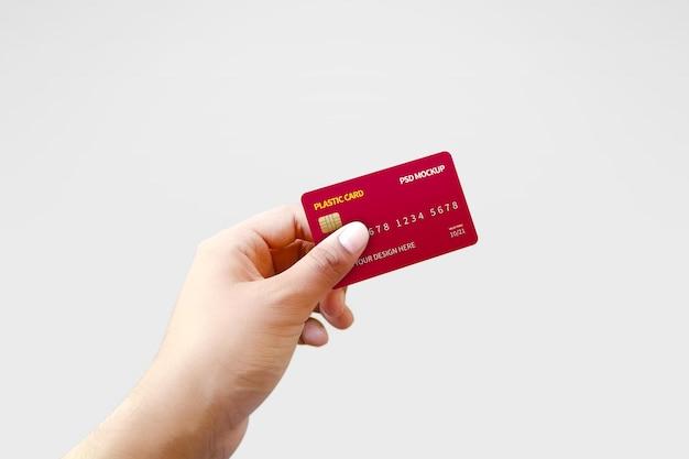 Наклонная пластиковая карта в руке макет