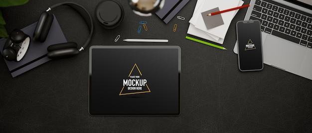 上面図の3dレンダリング、タブレット、ラップトップ、スマートフォンのアクセサリと消耗品を備えたダーククリエイティブなフラットレイワークスペース