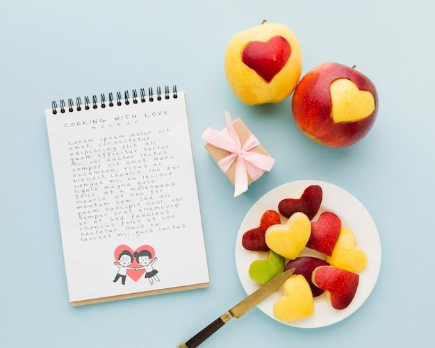 Вид сверху на яблоки и блокнот