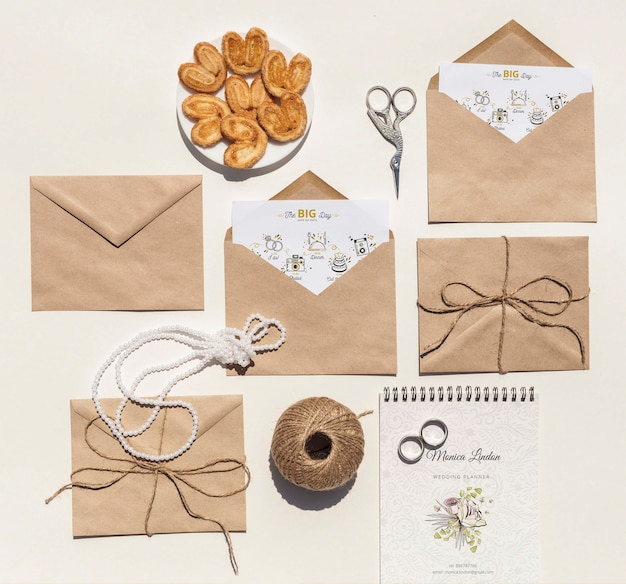 Top view arrangement of brown paper envelopes and wedding rings