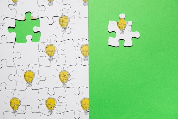Top view arrangement with puzzle on green background