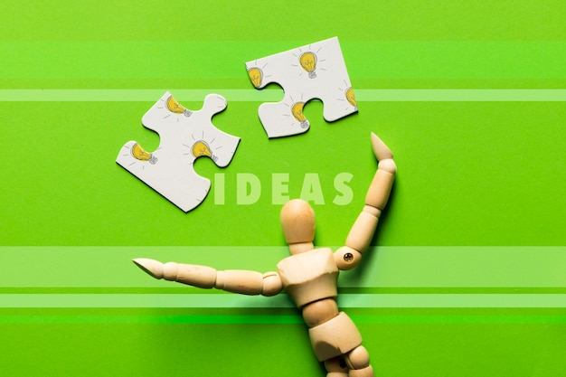 Top view arrangement with puzzle pieces and wooden robot