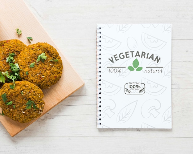 Top view arrangement with veggie food and notebook