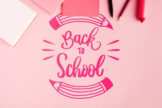 ピンクの背景で学校に戻るトップビュー