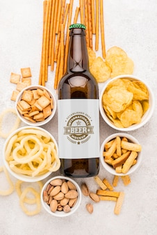 Top view of beer bottle with assortment of snacks