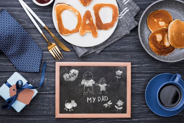 Top view of blackboard for fathers day with pancakes and gift