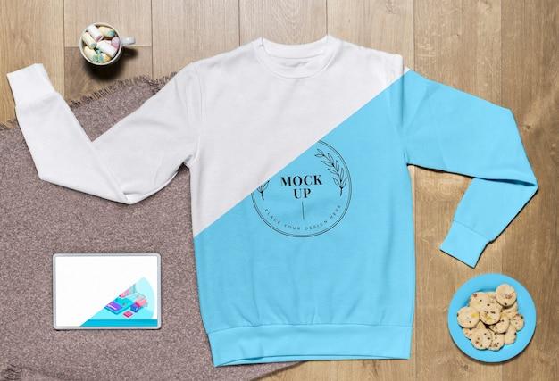 Mock-up di felpa con cappuccio blu vista dall'alto con biscotti e tablet