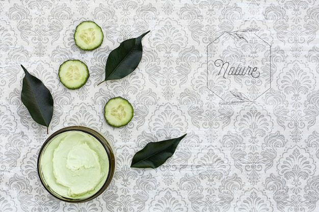Top view of body butter and cucumber on plain background mock-up
