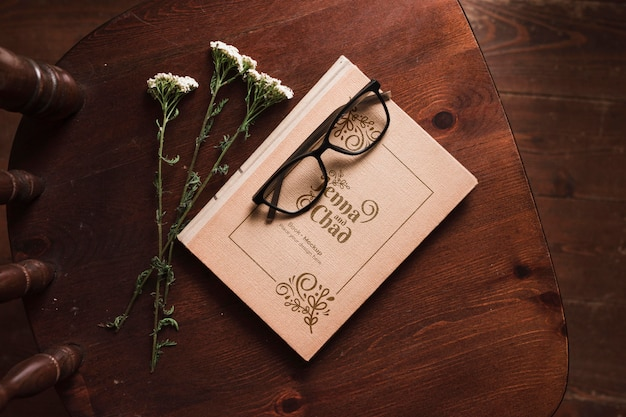 Top view of book on chair with flowers and glasses