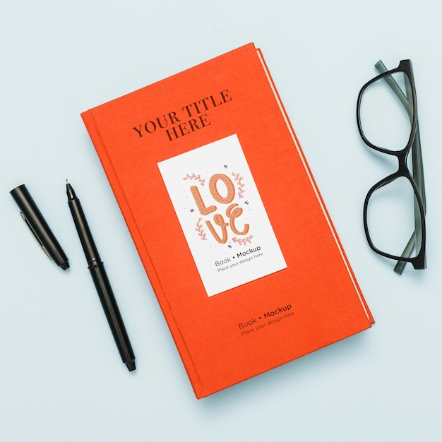 Top view of book mock-up with glasses and pen