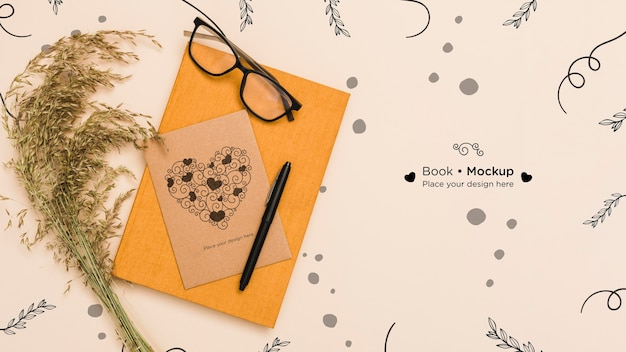 Top view of book with card and glasses