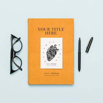 Top view of book with pen and glasses