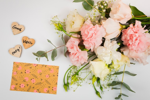 Top view bouquet of flowers next to cute envelope