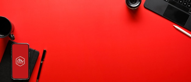 Top view of bright red desk with office supplies and mockup