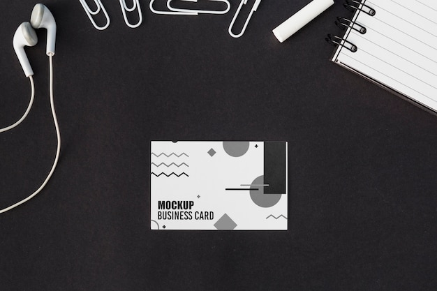 Top view of business card mock-up with earphones and paper clips