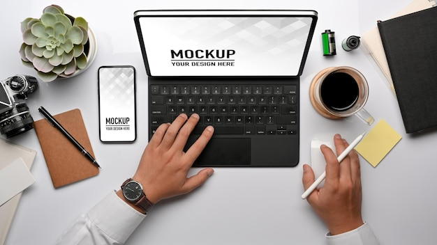 Top view of businessman hand working with tablet, smartphone mockup and office supplies