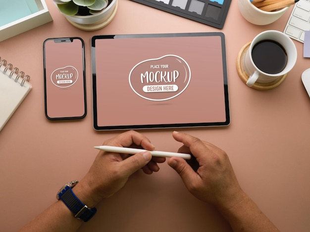 Top view of businessman hands holding stylus pen near devices mockup