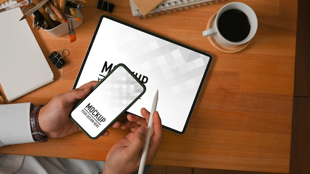 Top view of businessman working with smartphone and tablet mockup