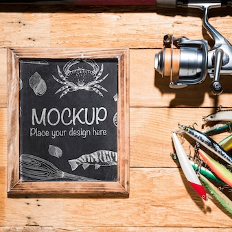 Top view of chalkboard with fishing rod and bait