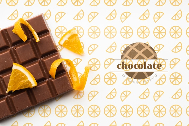 Top view chocolate with orange background mock-up