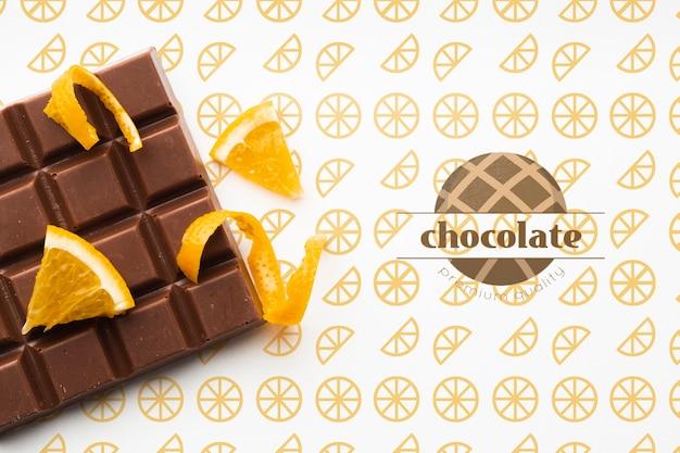 オレンジ色の背景のモックアップとトップビューチョコレート