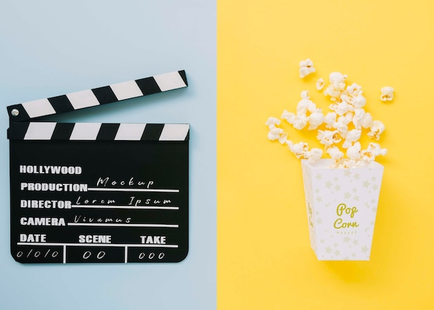 Top view of cinema clapperboard with popcorn and clapperboard