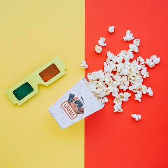 Top view of cinema popcorn in cup with glasses
