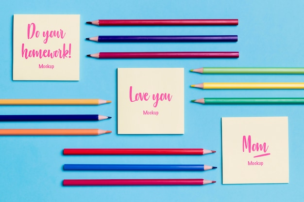 Top view collection of pencils and notes with mock-up