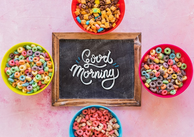 Top view of colorful cereals and chalkboard on plain background