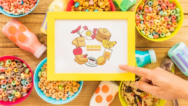 Top view of colorful cereals and frame on wooden table