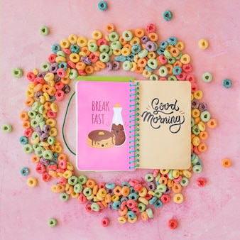 Top view of colorful cereals and notebook on plain background