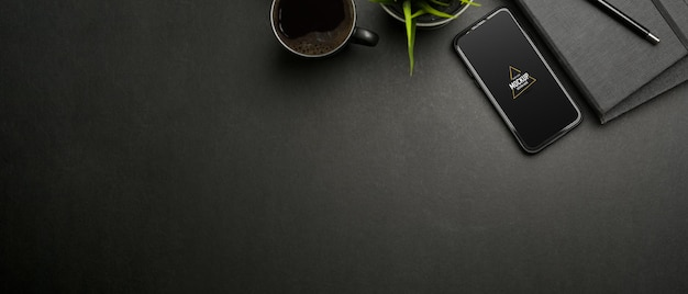 Top view of dark workspace with smartphone mockup, stationery and cup