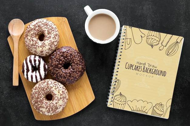 Top view of donuts with coffee and notebook