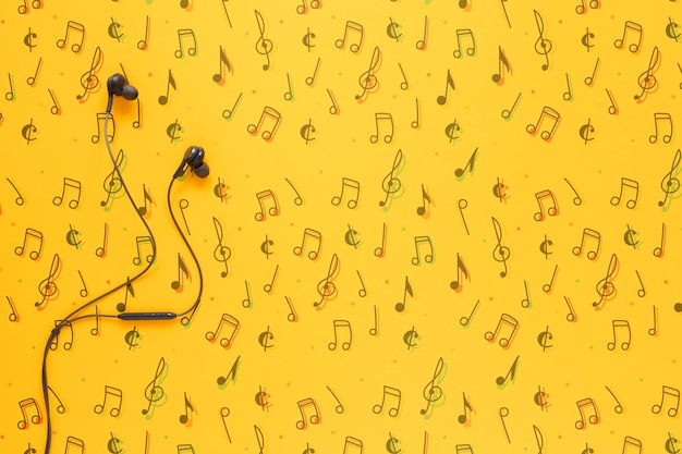 Top view of earphones on yellow background with copy space