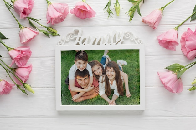 Top view of family frame and flowers on wooden background