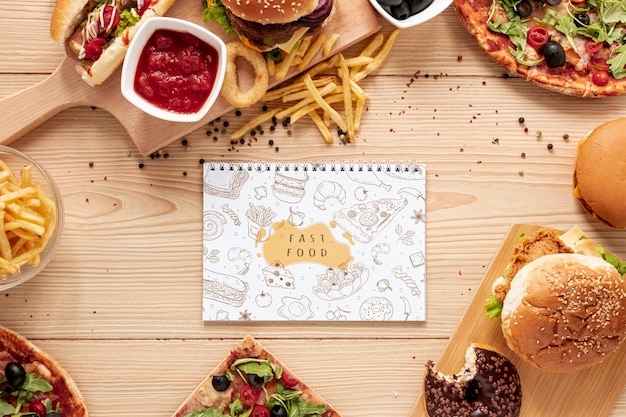 Top view of fast food on wooden table with notebook mock-up