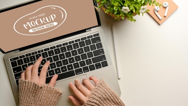 Top view of female hands typing on laptop mockup on white table decorated with plant pot